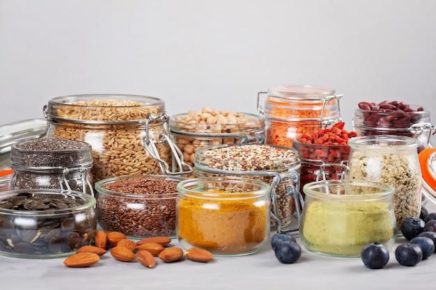 Verschiedene superfoods wie goji-beeren, quinoa, chia, hanfsamen, leinsamen, kichererbsen, hafer, mandeln, heidelbeeren, kurkuma, matcha und lantillen. diät-bioproduktkonzept des strengen vegetariers, der vegetarischen gesunden ernährung