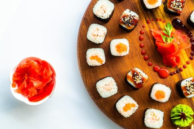 Verschiedene sushi auf einer runden holzoberfläche mit ingwer