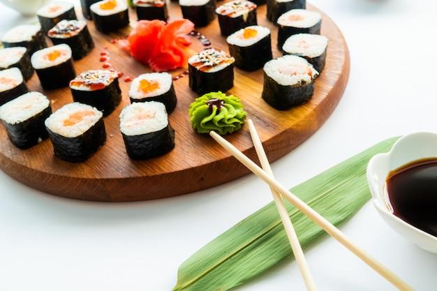 Verschiedene sushi auf einer runden holzoberfläche mit sojasauce und essstäbchen