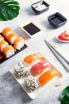 Verschiedene sushi auf keramikplatte mit koreanischen metallsticks auf heller steinoberfläche mit grünen blättern