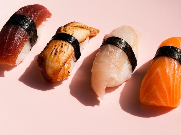 Verschiedene sushi auf rosafarbenem hintergrund