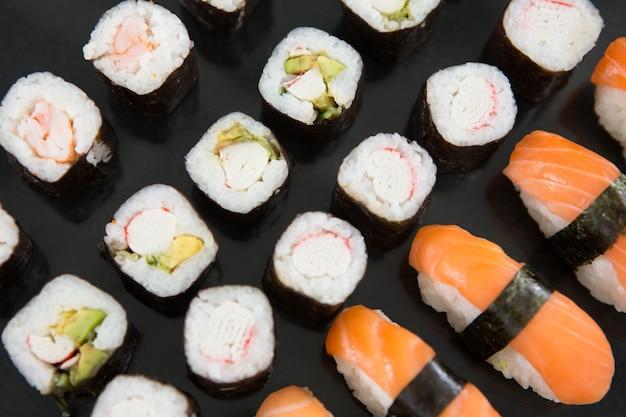 Verschiedene sushi auf schwarzem tisch