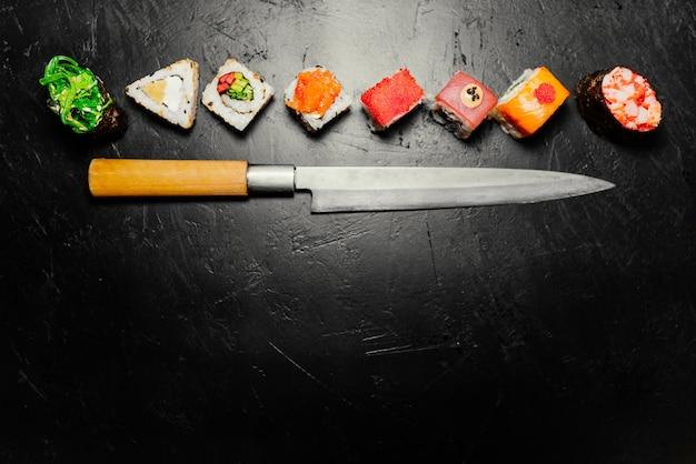 Verschiedene sushi mit japanischem messer auf schwarzem steinschieferhintergrund. sushi auf einem tisch.