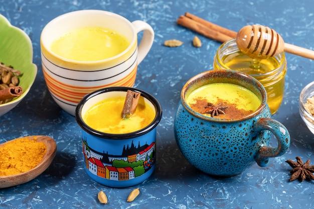 Verschiedene tassen mit goldener kurkuma-milch und zutaten zum kochen vor blauem hintergrund. nahaufnahme, selektiver fokus.
