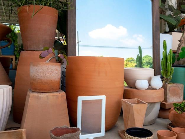 Verschiedene terrakotta-blumentöpfe neben dem spiegel im shop angeordnet. leerer geometrischer keramikpflanzer.