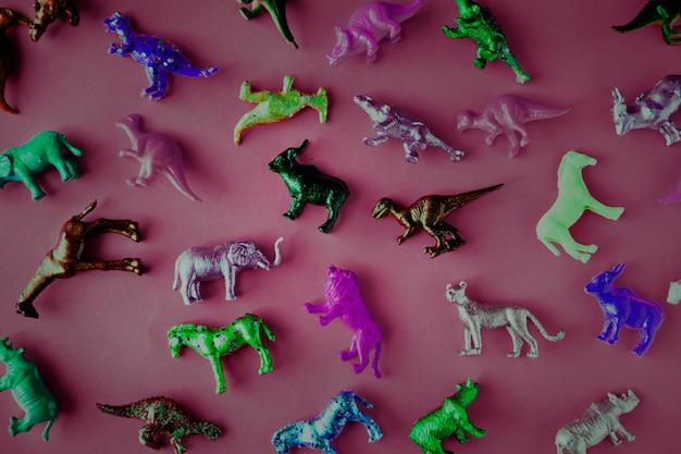 Verschiedene tierspielzeugfiguren in einem bunten hintergrund