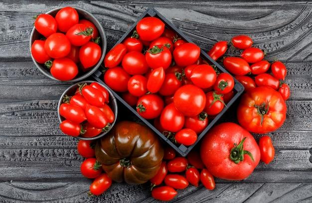 Verschiedene tomaten in holzkiste, mini-eimer auf einer grauen holzwand. draufsicht.