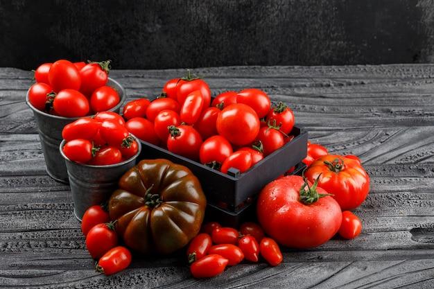 Verschiedene tomaten in holzkiste, mini-eimer auf grauer holz- und dunkler wand, hohe winkelansicht.