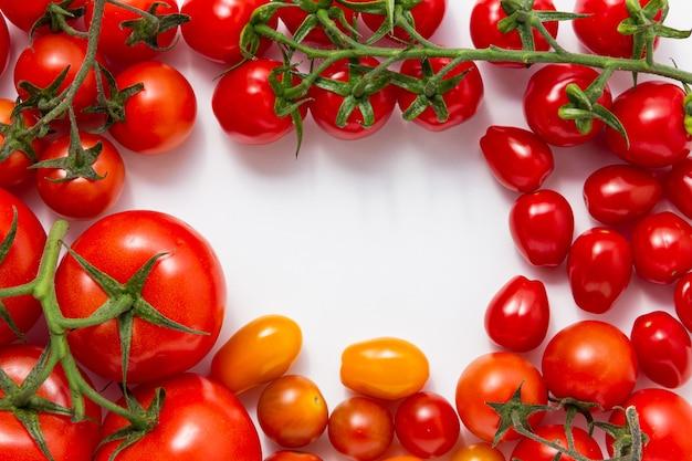 Verschiedene tomatensorten auf weißem hintergrund. draufsicht auf frisches gemüse.