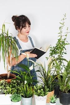 Verschiedene Topfpflanzen vor dem weiblichen Floristen, der Tagebuch hält