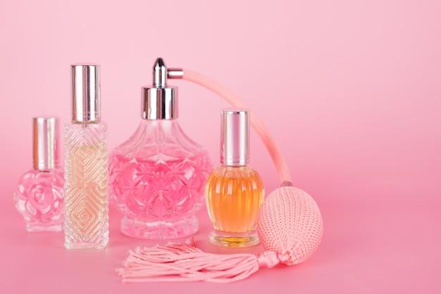 Verschiedene transparente parfümflaschen auf rosa hintergrund