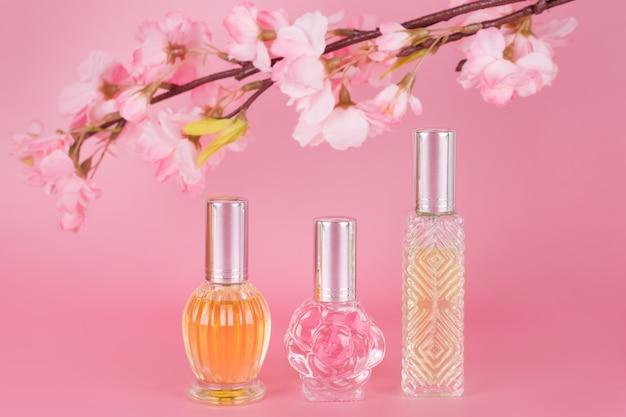 Verschiedene transparente parfümflaschen mit frühlingsblühendem ast auf rosa hintergrund