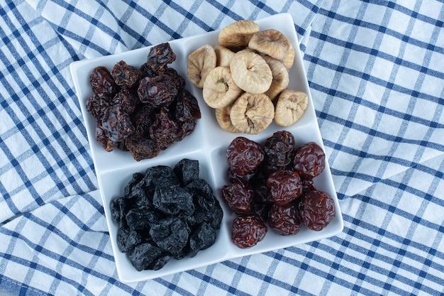 Verschiedene trockenfrüchte in schüssel, auf dem geschirrtuch, auf dem marmortisch.
