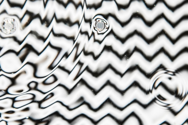 Verschiedene tropfengrößen des wassers auf einer schwarzweiss-pooloberfläche