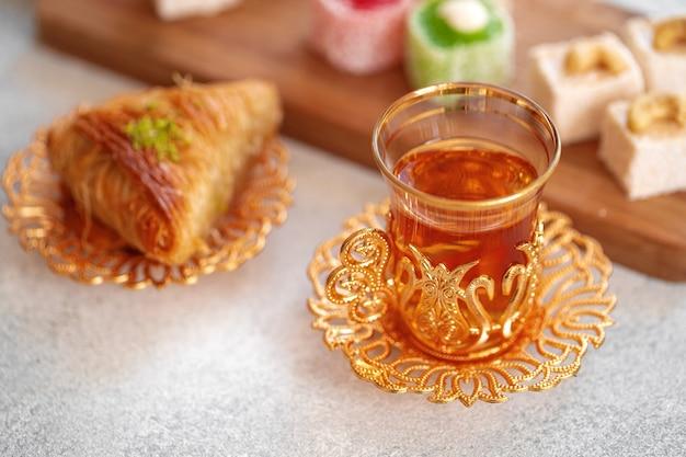 Verschiedene türkische süßigkeiten und eine tasse tee auf weißem strukturiertem hintergrund, nahaufnahme