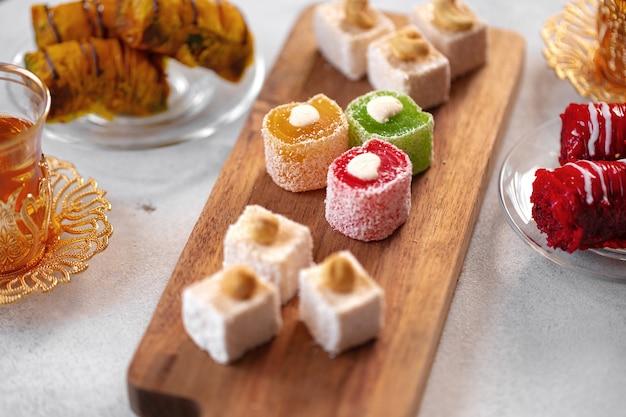 Verschiedene türkische süßigkeiten und eine tasse tee auf weißem strukturiertem hintergrund