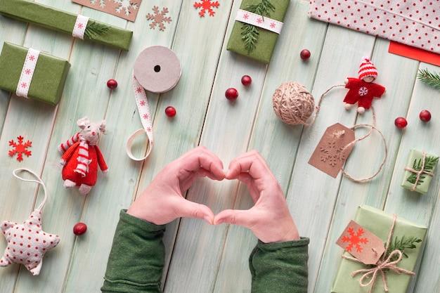 Verschiedene umweltfreundliche dekorationen für weihnachts- oder neujahrswinterferien, bastelpapierpakete und handgefertigte geschenke ohne abfall. flach lag auf holz, hände in grünen ärmeln zeigen herzzeichen.