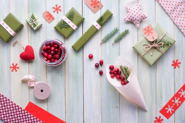 Verschiedene umweltfreundliche dekorationen für weihnachts- oder neujahrswinterferien, bastelpapierpakete und wiederverwendbare geschenke ohne abfall. flach auf holzbrettern liegen, cranberry in sperrholzkegel mit grünen blättern.