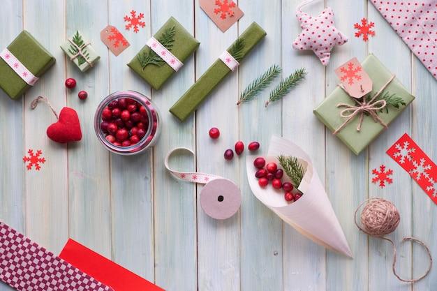 Verschiedene umweltfreundliche dekorationen für weihnachts- oder neujahrswinterferien, bastelpapierpakete und wiederverwendbare geschenke ohne abfall. flach lag auf holzbrettern, cranberry in sperrholzkegel mit tannenzweigen.