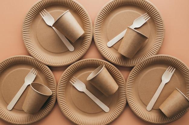 Verschiedene umweltfreundliche kraftpapierverpackungen, gabel, tasse und teller, behälter zum mitnehmen. null abfall und recycling-konzept. hochwertiges foto