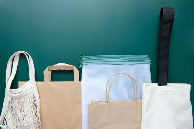 Verschiedene umweltfreundliche verpackungen auf grünem grund.