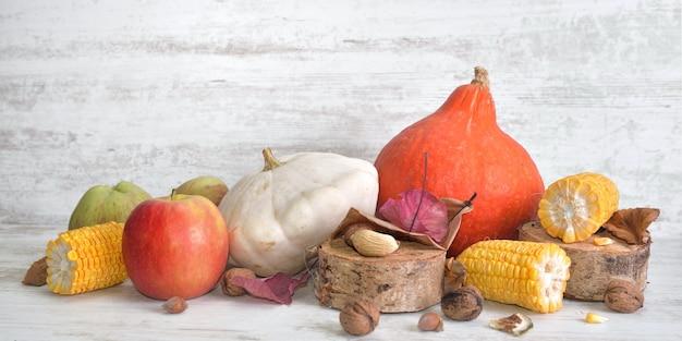 Verschiedene und farbenfrohe herbstliche gemüse und früchte mit in stücke geschnittenem maiskolben