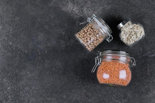 Verschiedene ungekochte müsli, körner für gesundes kochen in gläsern. ausgeglichenes nährendes nahrungsmittelkonzept