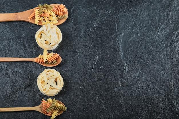 Verschiedene ungekochte nudeln auf holzlöffeln auf dunklem hintergrund.