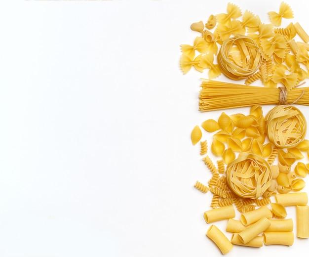 Verschiedene ungekochte nudeln. draufsicht. rohe nudeln mit zutaten zum kochen. lebensmittelkonzept