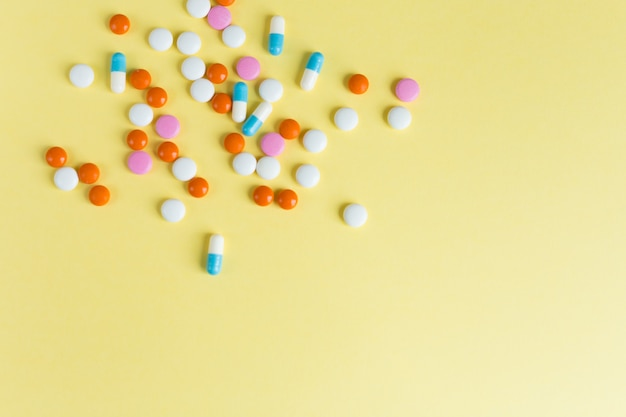 Verschiedene verschiedene medizinpillen, tabletten auf gelbem hintergrund. viele pillen und tabletten mit platz für text. gesundheitsvorsorge. draufsicht. speicherplatz kopieren. pharmazeutisches bild. flatlay. guter hintergrund