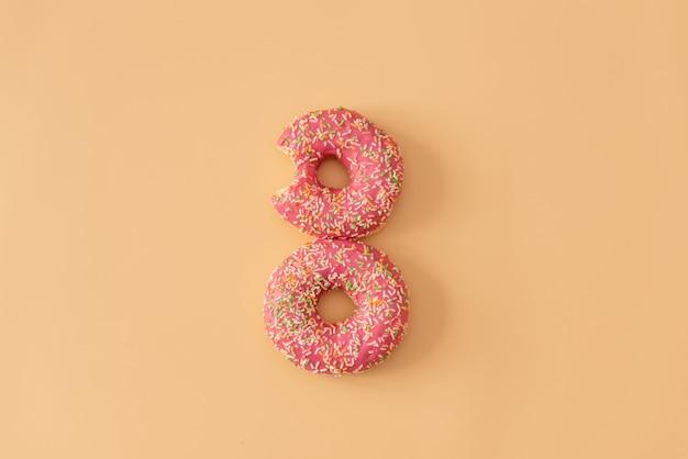 Verschiedene verzierte schaumgummiringe in der bewegung, die auf rosa hintergrund fällt. süße und bunte schaumgummiringe, die in bewegung fallen oder fliegen.
