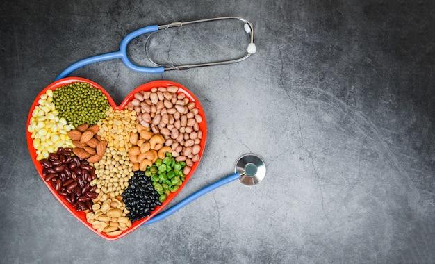 Verschiedene vollkornbohnen und hülsenfrüchte samen die linsen und nüsse, die auf rotem herzen bunt sind - mischen sie verschiedene bohnen der collage die erbsenlandwirtschaft des natürlichen gesunden lebensmittels für das kochen von bestandteilen