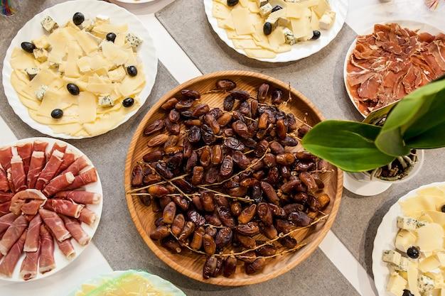 Verschiedene vorspeisen mit käse, fleisch und datteln für ein buffet