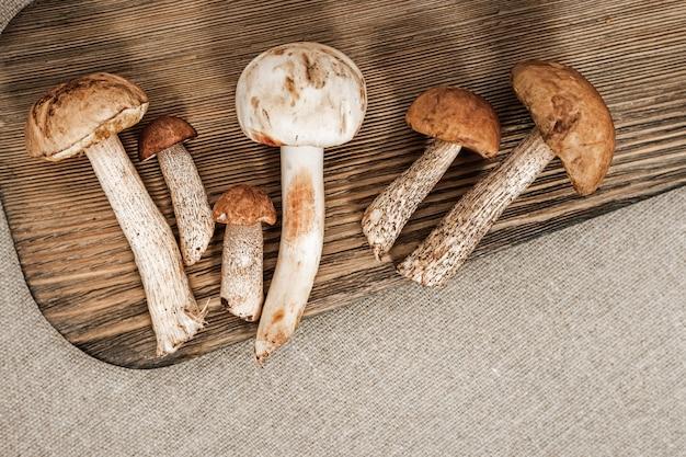 Verschiedene waldessbare pilze auf hölzernem hintergrund