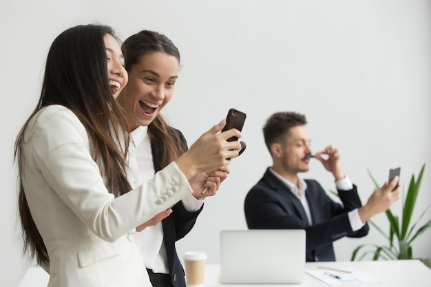 Verschiedene weibliche kollegen, die spaß mit smartphone im büro habend lachen
