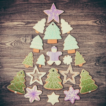 Verschiedene weihnachtsplätzchen in form eines weihnachtsbaumes auf der rustikalen holzoberfläche