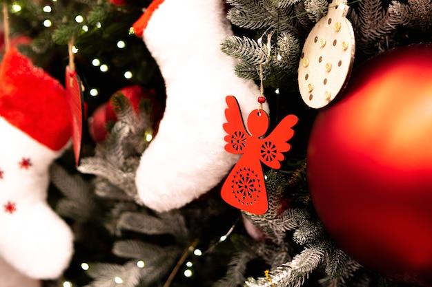 Verschiedene weihnachtsspielzeuge am weihnachtsbaum. tannenbaumspielzeug hautnah. urlaub dekoration spielzeug. frohe weihnachtsgrußkarte.