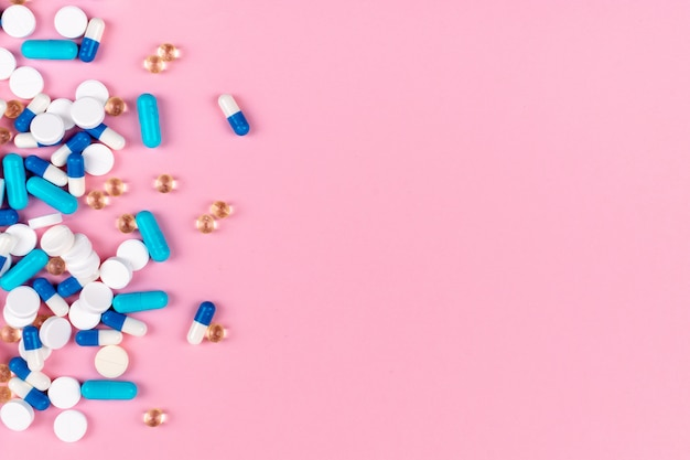 Verschiedene weiße und blaue pillen auf rosa hintergrund
