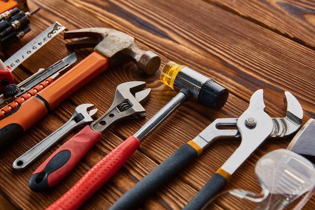 Verschiedene werkstattwerkzeuge, holztisch. professionelle instrumenten-, tischler- oder baumaschinenausrüstung, schraubendreher und schraubenschlüssel, pfähle und metallscheren