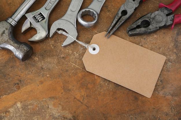 Verschiedene werkzeuge auf rustikaler hölzerner arbeitsplatte mit braunem tag
