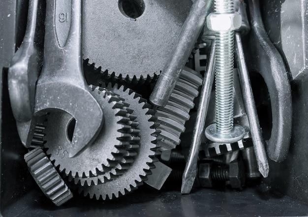 Verschiedene werkzeuge, schraubenschlüssel, zahnräder im kasten