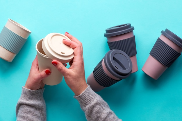 Verschiedene wiederverwendbare kaffee- oder teetassen oder magazine aus bambus mit silikonisolierung. hände öffnen den silikondeckel. flache lage, blauer papierhintergrund. umweltfreundliche null-abfall-lösung für einen nachhaltigen lebensstil.