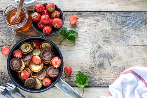 Verschiedene winzige pfannkuchen müsli in einer pfanne mit honig und erdbeeren