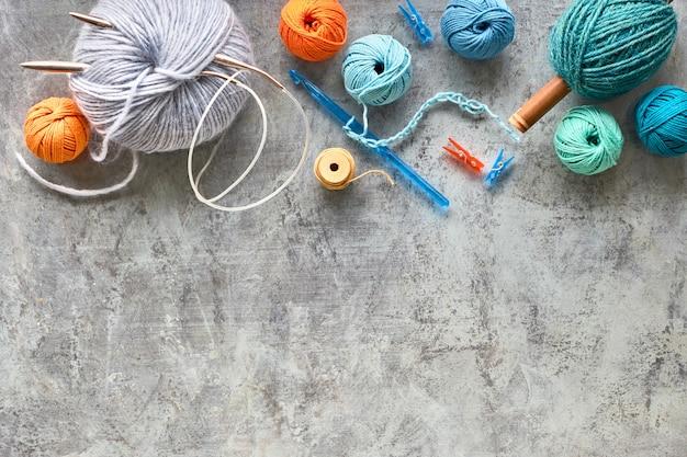 Verschiedene wollgarn und stricknadeln, kreativer strickhobbyhintergrund mit textraum