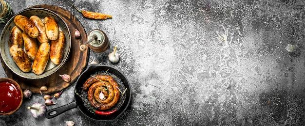 Verschiedene würste in pfannen mit knoblauch und gewürzen auf rustikalem hintergrund