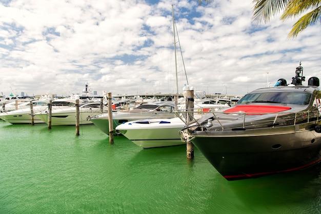 Verschiedene yachten in miami marina bay am südstrand auf dem wasser in der bucht am sonnigen tag mit wolken am blauen himmel