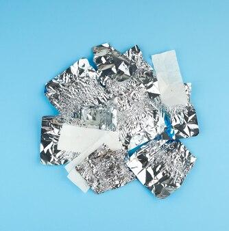 Verschiedene zerknitterte weiße papiere und folien verwendeten bonbonpapier auf blau