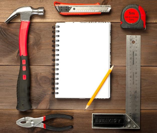 Verschiedene zimmerei, reparaturwerkzeuge, notizblock auf holz