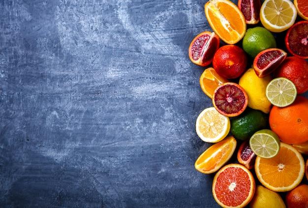 Verschiedene zitrusfrüchte auf einem blauen hintergrund