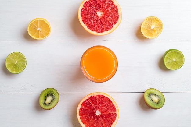 Verschiedene zitrusfrüchte mit einem getränk auf der tischplattenansicht